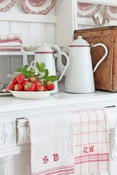 I love everything about this photo.  Enamel ware, tea towels, plate rack, plates and wicker!  Farmhouse look at it's best.