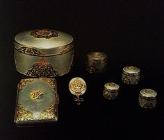 A set of betel leaf and areca nut boxes, consisting of one large box ,four small ones and a mirror. A cigarette box of pewter trimmed with gold,made to order from J  Benson,England.   All of the royal initials of H.M.King Chulalongkorn in enamel.