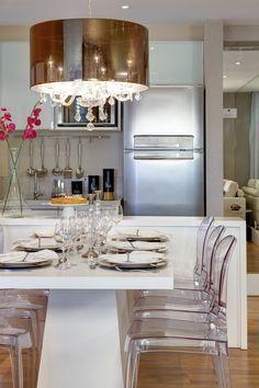 Sala de jantar com cadeiras transparentes e lustre de cristais integrada com a cozinha