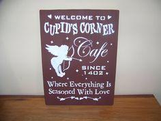 Primitive Rustic Burgundy Cupid Cafe Woodcraft Stencilled Sign for Valentine's Day. $14.00, via Etsy.
