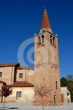 Photo made at the bell tower and the church of Vigo a town in the province of Padua in Veneto (Italy). In the image we see in the foreground the bell tower with the tip cone, the parteposteriore of the church and finally the intense blue of the sky.