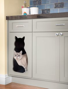 Blue, a Siamese-tabby mix, accesses her litter box in private, thanks to a cutout cat cave. The cabinets have traditional out-swinging doors so the litter box and other pet supplies are within easy reach.
