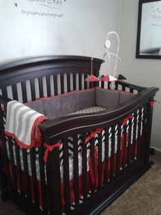 Red trim and crib skirt with grey and black custom crib bedding to reflect the colors in the Baby Einstein baby mobile