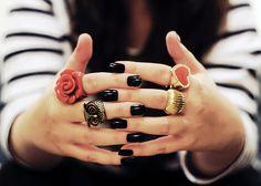 Nautical stripes, short, black nails, gaudy rings.