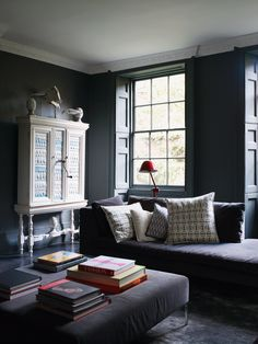 Darker, north-facing rooms can look cold when painted gray (that steady northern light has a bluish cast). Try a strong shade paired with pops of bright color to make the space feel cozy.