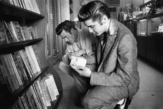 Elvis Searches for an Interesting Magazine  With his cousin Junior Smith, Elvis reviews the many magazines found in the coffee shop of the Hotel Jefferson, in Richmond, VA. Later that afternoon he will perform at the Mosque Theater in the Elvis Presley Show. June 30, 1956.