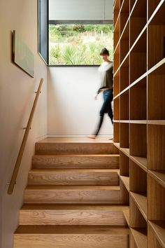 Escalera subida desde el salón a la primera planta. Estantería continúa hasta la 2º planta