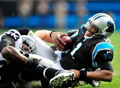 Cam Newton #1 of the Carolina Panthers is sacked by Tommy Kelly #93 of the Oakland Raiders during play at Bank of America Stadium on December 23, 2012 in Charlotte, North Carolina.