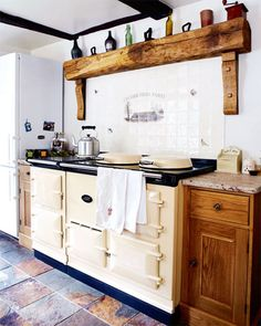 Rustic beam and Aga range. Might have to move to England to find a kitchen like this.