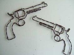 "RUSTY BARBED WIRE PISTOL PAIR: Here is a pair of pistols to hang above a mirror, sign, picture or alone. These are approximately 13"" across the widest point."