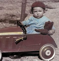 Vintage tinted photo of French boy taking is Teddy bear for a spin in his roadster!