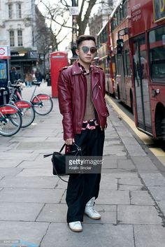 The Bold Concept founder Jocelyn Yih wears a Zara biker jacket, Raf Simons shirt and trousers, Prada jumper, Loewe bag, Dior sunglasses and Maison Margiela trainers on day 3 of London Collections: Men on Januay 10, 2016 in London, England.