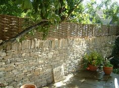 wood fence on top of loose stone wall Willow Garden, Trellis Fence, Garden Privacy, Garden Screening, Outdoor Stone, Stone Fence, Dry Stone, Natural Garden, Garden Stones