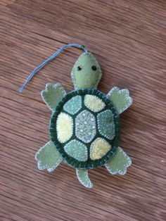 Green felt turtle with calico shell details hand-stitched with two shades of blue floss. Blanket stitched around edge of head and feet with light blue