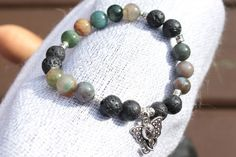 What you see is what you get - this is the only one of this bracelet I will make! Get it before its gone! - 8mm multicolored Indian agate beads. - 8mm black lava stone be ads. - Silver tone elephant face charm and accents. - 6.5 Inches un-stretched (approximately). This bracelet best fits people with a small/medium frame. - Ships from Canada.  This awesome bracelet is colorful without being loud, and lava stone is a natural diffuser. This bracelet looks good on anyone and makes a wonderful…