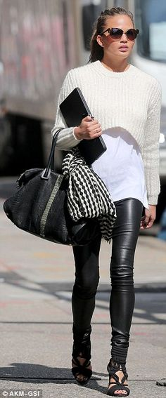 belly-baring jumper over a long white shirt, black leather leggings, and Balmain gladiator heels