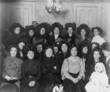 A large group of women wearing dark, early 20th century clothing pose for the camera.