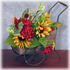 Timeless Charm Sunflower Geranium Bouquet - The late summer months are captured in this delightful bouquet featuring sunflowers and red geraniums. A smattering of clover stems and green clover type filler round out the bouquet. 50th Wedding Anniversary, Anniversary Parties, Late Summer, Summer Months, Wheelbarrow Garden, Red Geraniums, Sunflowers, Tablescapes, Planter Pots