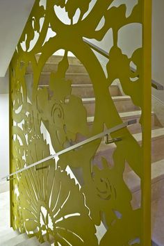 A sheet of metal has been laser cut and painted green to create an artistic floral print that doubles as both a safety railing for the stairs and an artistic installation to look at while you go up and down the stairs.