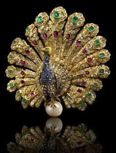 A gem-set and diamond peacock brooch, Gustave Baugrand, circa 1865,   the body pavé-set with sapphires and diamonds, extending articulated cushion and rose-cut diamond plumes, enhanced by vari-cut emeralds and rubies, perched on a cultured pearl, measuring approximately 8.50mm.; signed Baugrand for Gustave Baugrand; mounted in eighteen karat gold and platinum; length: 2 1/8in. (pearl not tested for origin, brooch fitting is detachable). via Bonhams.