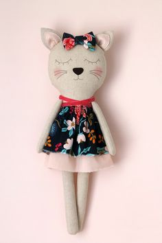 ♥ This sweet cat is the perfect addition to a childs bedroom or nursery and makes a great birthday or baby shower gift. It features a two-layered dress and a bowtie. Made to be loved, this is a truly heirloom doll. ♥  - The cat has a floral two-layered dress made with a cotton lightweight fabric stitched to the its body. - The body is made with a cotton linen blend fabric and the face is machine stitched. - The cheeks are colored with a child-safe and non-toxic water based pigment. - The…