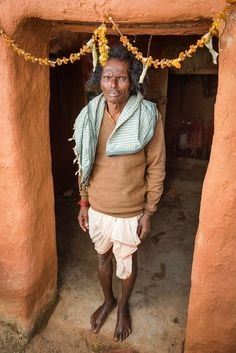 Witchdoctor Somaru stands in front of his self-build shrine which he made to honor the local village goddess. Chhattisgarh, India.