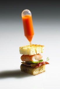 Eatertainment skewers a miniature lobster club with a pipette filled with lobster bisque