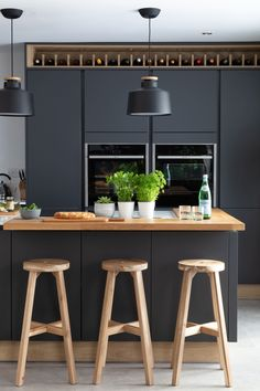Stunning modern handleless kitchen mixing dark grey and wood effect cabinets. Pictured H Line Sutton in Graphite with Portland Oak Cabinets. Photographed by Paul Craig