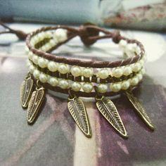 Pulseira estilo chan luu com fio de algodão marrom, pérolas, corrente e pingente folha ouro velho. <br>Fechamento em botão com duas regulagens de tamanho. (18 e 20 cm)