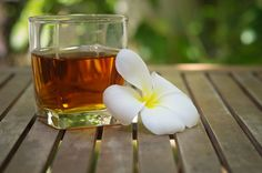 glass of tea blooming white plumeria flower on wooden table with
