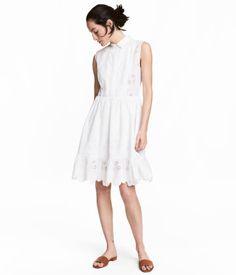 Blanco. Vestido de algodón con bordado inglés. Modelo con cuello, botones ocultos arriba, costura en la cintura, falda con volante en el bajo y cremallera