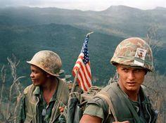 Marines descargan y se mueven por una zona llena de ramas ell 17 de diciembre de 1969