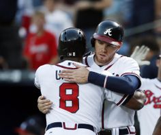 Atlanta Braves left fielder Justin Upton (8) gets a hug from first baseman Freddie Freeman (5) after hitting a three-run home run in the first inning of a baseball game.