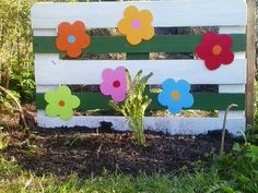 A cute garden accent fence piece. Paint an old pallet and embellish it with wooden cut out shapes of flowers, birds, butterflies. It really brightens up a small space.