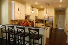 Custom kitchen with contemporary pendant lighting by Kurk Homes