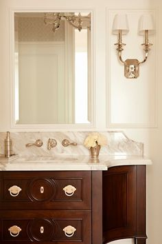 Gorgeous bathroom with traditional mahogany colored vanity with silver hardware alongside a marble countertop with undermount sink and wall mounted faucet.