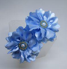 """Tiara forrada com fita de cetim, com duas flores azul no estilo """"Carinha de Anjo"""". Pode ser feita na cor de sua preferência."""