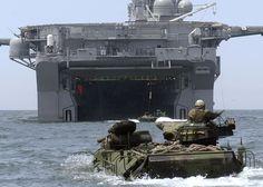 USMC Assault Amphibious Vehicles (AAVs) approach the well deck of the USS Bonhomme Richard.