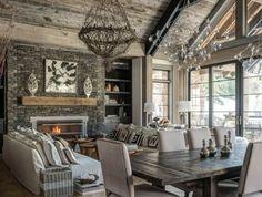 maison ossature bois, table en bois et chaise en bois et cuir, canapés blancs par terre, cheminée en pierre, suspension intéressante en branches de bois, salon rustique