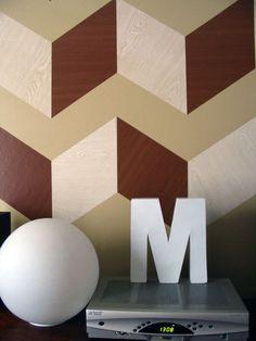 A parede bege mortinha se transformou na vedete da casa! Também foram usadas tiras de Papel Contact de cores de madeira diferentes. Mais detalhes e fotos em http://www.apartmenttherapy.com/before-after-maudes-graphic-wo-78683