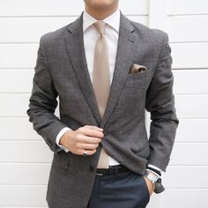 Cream knit necktie paired with brown jacket and charcoal pants