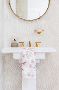Neutral powder room with a round mirror, printed wallpaper, and a sink