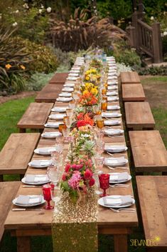 Glittery gold table runner with rainbow colored floral centerpieces - all over a wooden table #wedding #rustic #chic #tablescape #gold