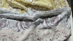 Hand dyed silk in a soft blue. gray fading to a gold, then a black inked rose and leaf design. Soft and flowing, A stunning accent piece. 20x60 inches The best care instruction for this scarf is to, Wash gently in cold water with a drop of natural soap. Rinse thoroughly. To dry: use a