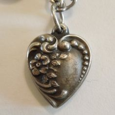 This WWII-era heart has an asymmetrical design with a forget-me-not flower and foliage bordered with scrollwork on the left, and lovely graduated