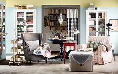 Woonkamer met twee IKEA fauteuils, voetenbank, tafeltjes en boekenkasten