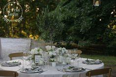 Un piccolo alberello di ulivo come centrotavola, circondato da candele e piccoli vasetti con fiori: peonie, rose, lisianthus...