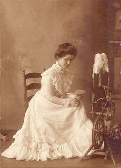 1903  Portrait of Blanche Bean Musselman seated beside a spinning wheel, reading a letter wearing formal white dress. (c1903)