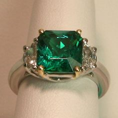 platinum ring with zambian emerald and diamond side stones