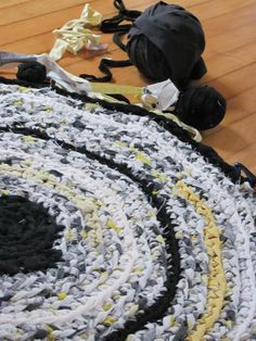 Upcycled Fabric Rug in White, Yellow, Black and Gray.  made with a repurposed bed sheet and a bunch of t-shirts cut into fabric strips, then hand-crocheted together.